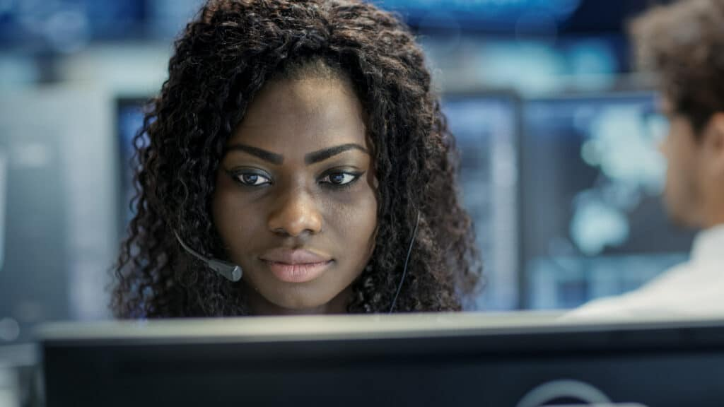 African American woman with a headset on looking at a computer